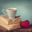Cup of coffee standing on old books — Stock Photo