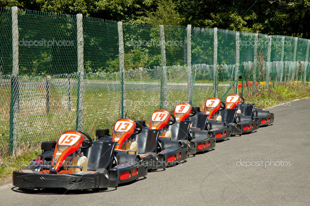 Carting-cars in a row in front of a fence for background use — Stock Photo #12469540