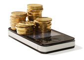Golden coins on cellular mobile phone — Stock Photo