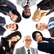 Group of business standing in huddle, smiling, low angle view — Stock Photo #20334165