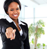 Smiling black business woman pointing on camera in office — Stock Photo