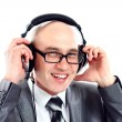 Smiling businessman wearing headphones looking to camera, listening to music — Stock Photo