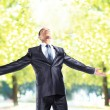 Happy businessman standing outside with arms outstretched — Foto Stock