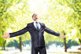 Happy businessman standing outside with arms outstretched — Stockfoto