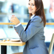 Young businesswoman sitting at desk and working. Smiling and looking back at camera — ストック写真
