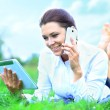 Portrait of young beautiful smiling woman with tablet pc and talking on  mobile phone, outdoors — Stock Photo