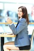 Joven empresaria sentado en el escritorio y trabajar. sonriendo y mirando hacia atrás en cámara — Foto de Stock