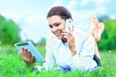 Portrait de jeune femme souriante belle avec les tablet pc et parler au téléphone portable, à l'extérieur — Photo