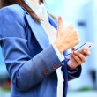 Pretty young business woman using mobile phone outdoor and ok sign — Stock Photo #32351213