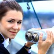Businesswomlooks through telescope on city building — Stock Photo #32357319