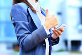 Pretty young business woman using mobile phone outdoor and ok sign — Stock Photo