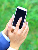 Woman using mobile smart phone in the park. — Stock Photo