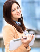 Businesswoman in coat working on digital tablet out of office overlooking cityscape — Stock Photo