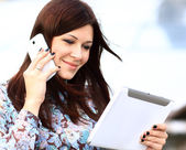 Young businesswoman talking digital tablet and mobile phone over building background — Stock Photo