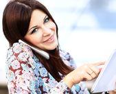 Gros plan d'une jeune femme d'affaires à l'aide de tablette numérique et téléphone mobile sur fond de construction — Photo