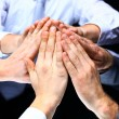 Stock Photo: Hands of business people forming pyramid in air.