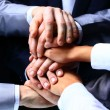 Diverse group of workers with their hands together in form of teamwork — Stock Photo