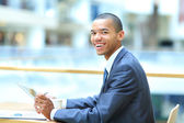 Image of young African man looking at camera with laptop near by — Stock Photo