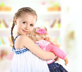 Cute little girl with a doll — Stock Photo