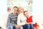 Familie met meisje zit op witte lederen sofa — Stockfoto