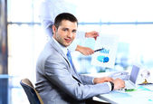 Portrait of cheerful businessman making notes and looking at camera — Stock Photo