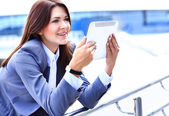 Businesswoman working on digital tablet outdoor over building background — Stock Photo