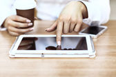 White tablet with a blank screen in the hands on wooden table — Stock Photo