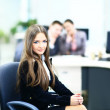 Portrait of a cute business woman with colleagues at the background — Stock Photo