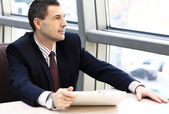 Business man looking away in window and working on tablet pc in his office — Stock Photo