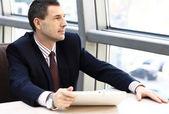 Affärsman tittar bort i fönstret och arbetar på tabletpc i hans kontor — Stockfoto
