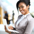 Business woman standing in foreground with laptop in her hands, — Stock Photo
