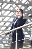Young business woman in the big city purposefully looking away and talk on phone — Stock Photo