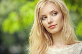 Beautiful young blond woman on abstract green background — Stock Photo