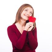 Woman holding heart shape and dreaming — Stock Photo