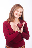 Smiling woman holding heart shape — Stock Photo