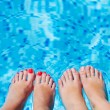 Women foot  splashing in swimming pool - Stock Photo