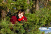 Young man smiling in winter forest — Stock Photo