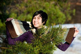 Beautiful young woman smiling in winter forest — Stock Photo