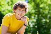 A young curly man in a forest — Stock Photo