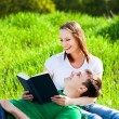 Lovers in the park are reading book — Stock Photo
