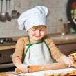 Lovely girl in a chef's hat cooking sweet cake — Stock Photo