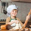 Lovely girl in a chef's hat cooking sweet cake - Stock Photo