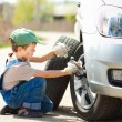 Boy changes the wheel — Stock Photo