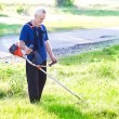 Senior man with lawn mower — Stockfoto