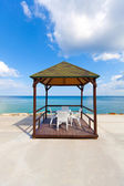 Empty chairs and gazebo by the beach. — Stock Photo