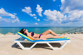 Beautiful girl in a bikini lying on a deckchair — Stock Photo