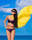 Beautiful girl in a bikini girl with a yellow cloth that develop — Stock Photo