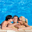 Sexy girls kissing a man in the swimming pool — Stock Photo #26301363