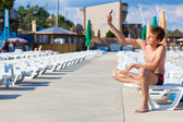 Man sitting on a sunbed, with mobile phone in hand — Stock Photo