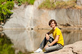 A young man sitting on the shores of Lake — Stock Photo